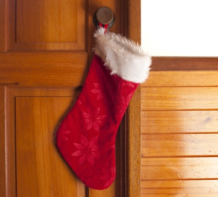 Empty red Christmas stocking hanging on a door